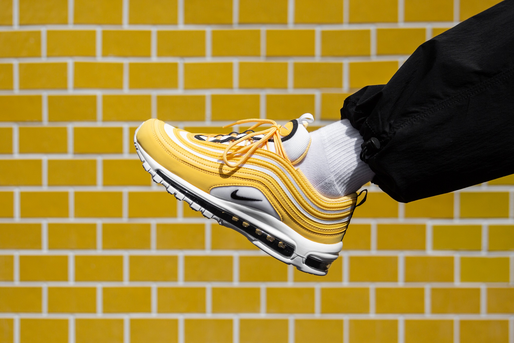 0960b28993 Nike is brining sunshine to its latest Air Max 97 release, which is  radiating waves topaz gold on the upper. The yellow tone is set against  white with black ...